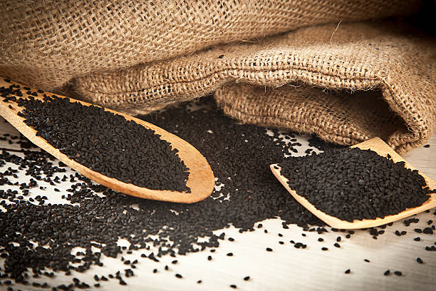 (Black cumin) on wooden spoon. Macro shot stock photo