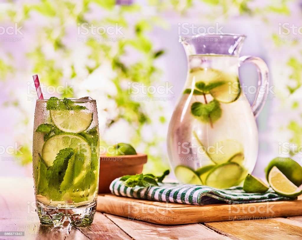 On wooden table is glass jug with transparent drink. stock photo