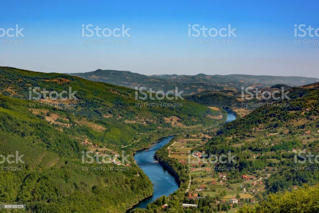 Once it was an important battle site that divided the Eastern and the Western Roman Empire,today the Drina river is the border between Serbia and Bosnia. Deep blue color of Drina, and green landscape. stock photo