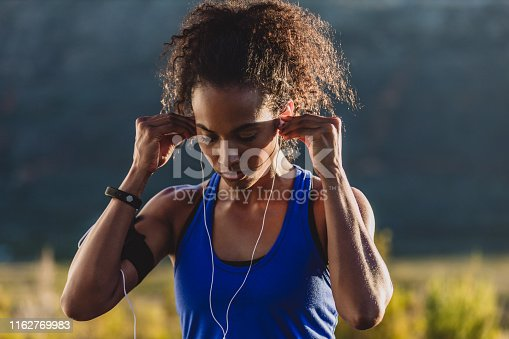 Cropped shot of a young woman wearing earphones while out for a run