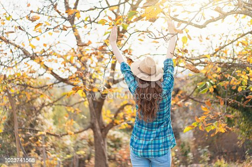 Rear view of an unrecognizable woman with a hat enjoying carefree autumn day in her backyard.