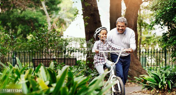Shot of an adorable little girl being taught how to ride a bicycle by her grandfather at the park