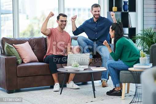 Shot of a group of young businesspeople cheering while using a laptop together in a modern office