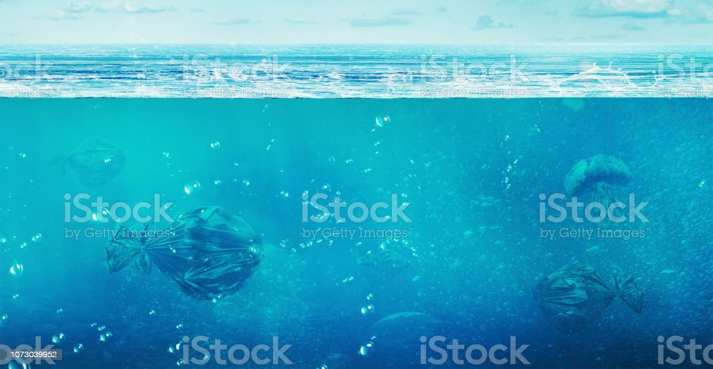 oncept of global pollution. In the open ocean floating trash bags in...