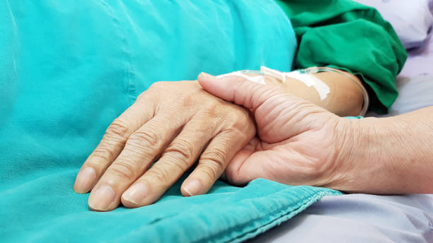 Oncologist doctor holding patient's hand in hospital. Showing all love, empathy, helping and encouragement. He has end stage cancer disease. Healthcare in end of life and palliative care concept stock photo