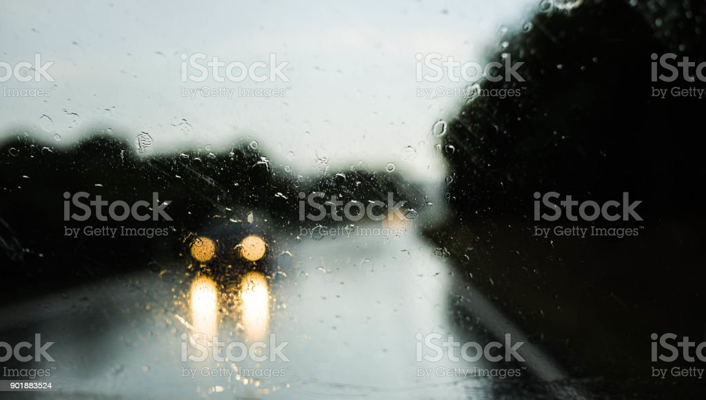Oncoming Car in the Rain - View through the Front Window of Car - on the Road stock photo