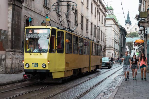 トロリー路面電車レール トラックの人々 の群衆の中に旧市街の歴史的なウクライナのポーランドの都市で onductor 立って線日中コーヒー カフェ ・ レストラン - ウクライナ ストックフォトと画像