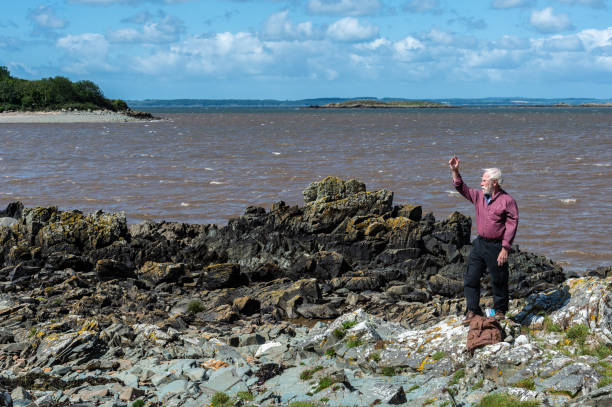 One active senior man at the coast on a sunny and windy day waving One retired man standing on a rock at the coast on a sunny windy day. The location is in Dumfries and Galloway, south west Scotland. johnfscott stock pictures, royalty-free photos & images