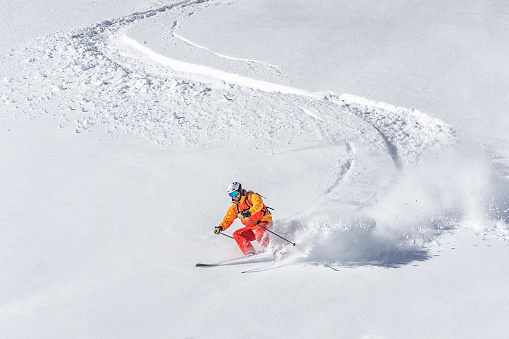 One adult freeride skier skiing downhill through deep powder snow