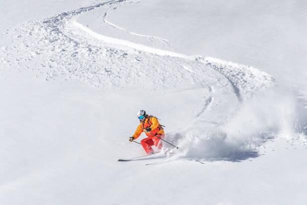 one adult freeride skier skiing downhill through deep powder snow - ski foto e immagini stock