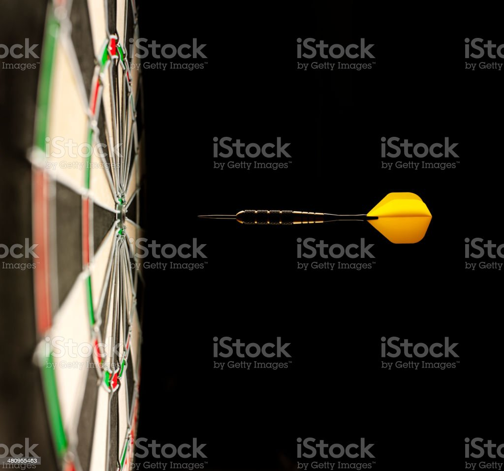 One Airborne Dart Hitting the Target on a Dartboard stock photo