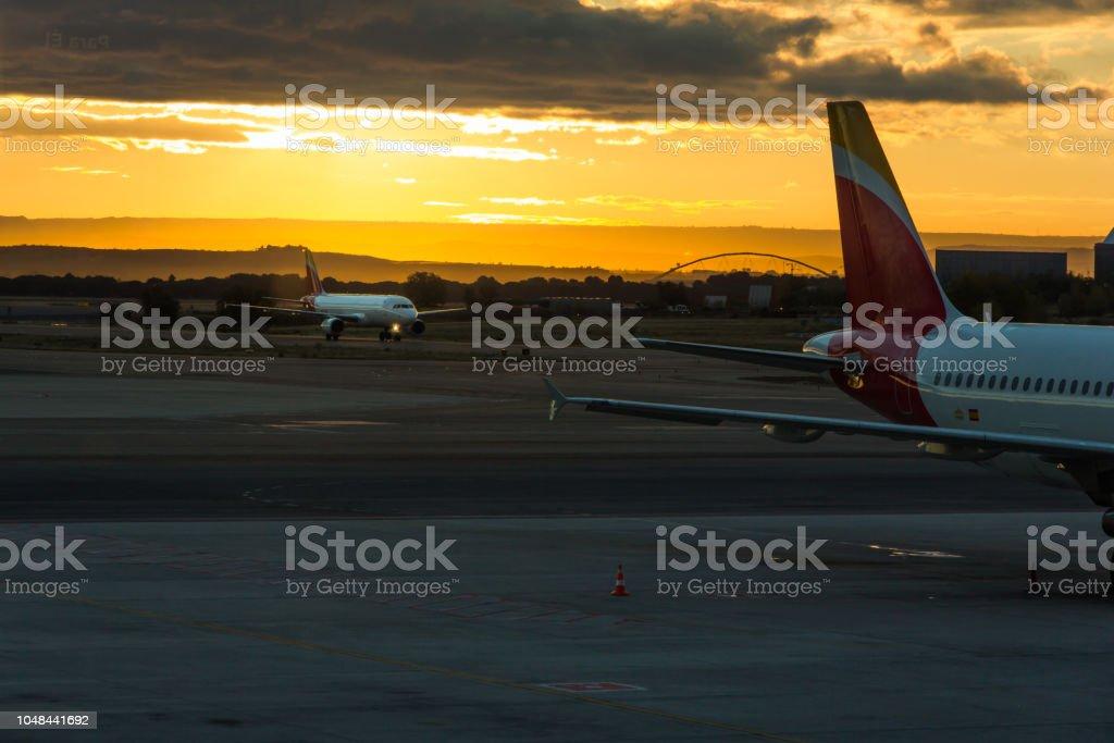 Un avion au roulage et un autre stationnement à l'aéroport à l'aube - Photo