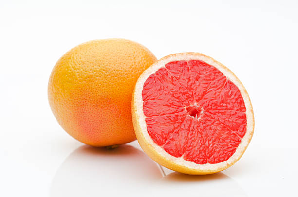 one and a half grapefruits on a white background - grapefruit stock photos and pictures