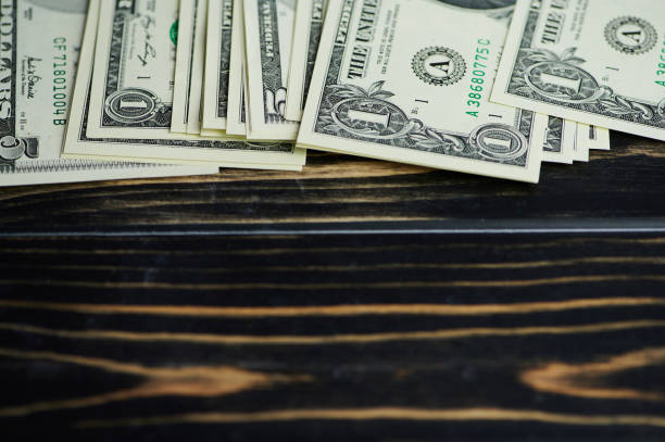 one and five dollar banknotes on a wooden surface stock photo