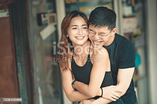 one asian chinese couple wearing black color t-shirt hugging from behind and smiling