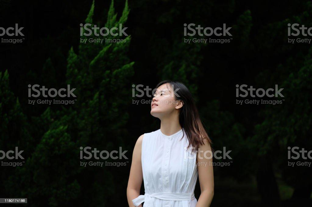Een Aziatisch meisje in puur witte rok, staande voor dennenboom onder natuurlijk daglicht. - Royalty-free Achtergrond - Thema Stockfoto