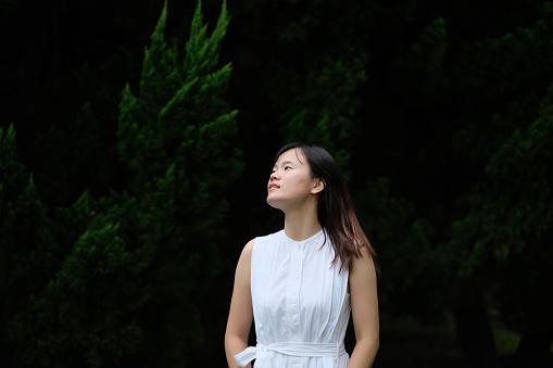 Een Aziatisch Meisje In Puur Witte Rok Staande Voor Dennenboom Onder Natuurlijk Daglicht Stockfoto en meer beelden van Achtergrond - Thema