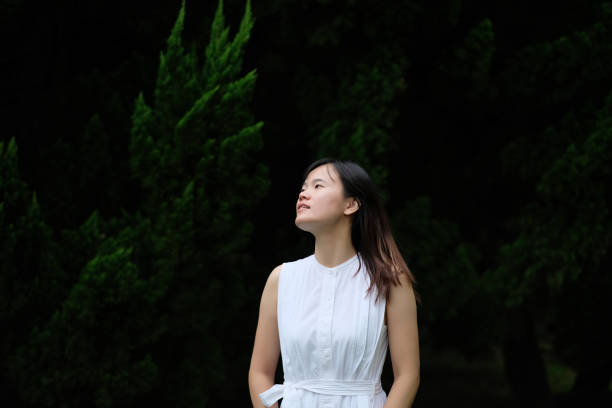 een aziatisch meisje in puur witte rok, staande voor dennenboom onder natuurlijk daglicht. - portait background stockfoto's en -beelden