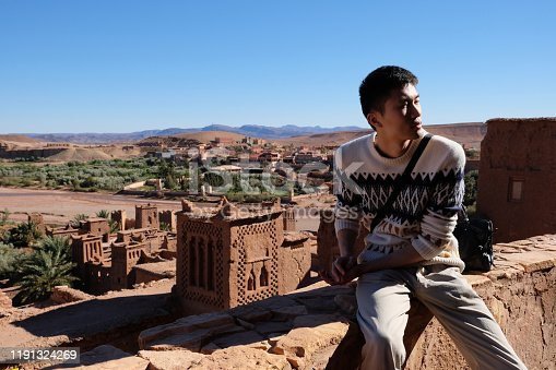 872393896 istock photo one Asian young man sitting on old brown city wall of Ait Ben Haddou under sunshine. 1191324269