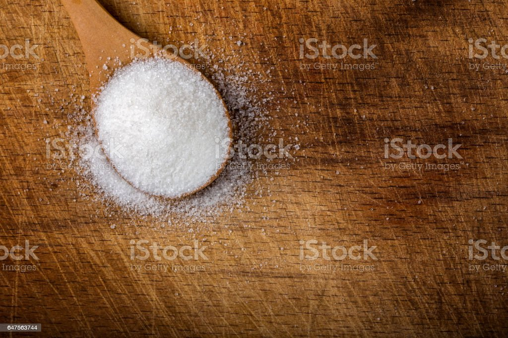 One bamboo spoon filled with white sugar on wood stock photo