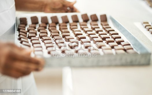 Close-up of a female chef holding a baking tray with chocolate dipped biscuits at a bakery