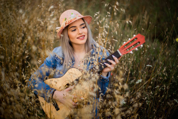 One beautiful young women is playing guitar at field