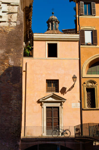one bicycle standing near a door against the wall on a solitary street in the city center of the capital of italy, rome. warm fall morning, vibrant blue sky, calm atmosphere - rome road central view foto e immagini stock