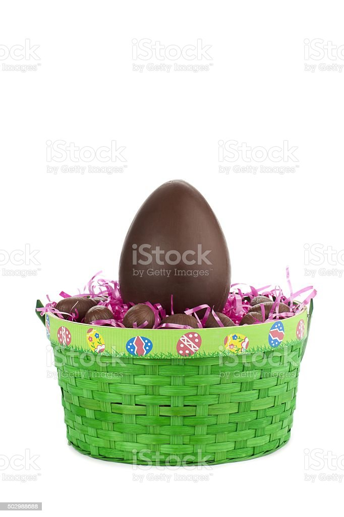 one big brown easter egg in green basket stock photo