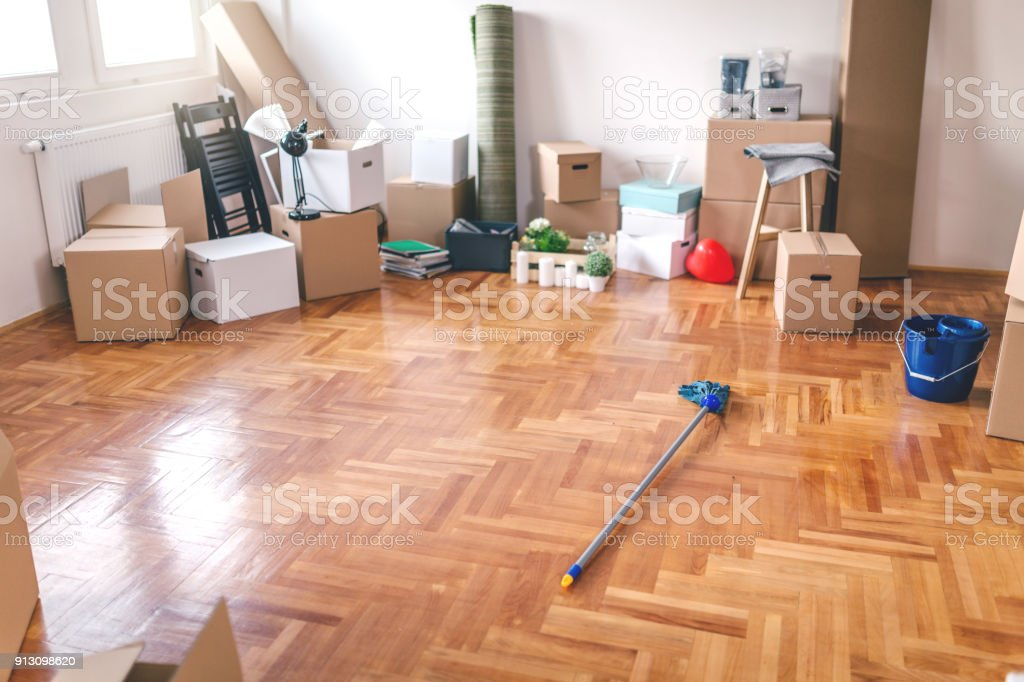 Unpacked new apartment with a messy floor, ready for cleaning.