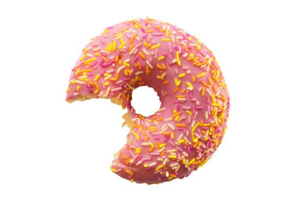 ein biss fehlt der donut mit rosa zuckerguss und bunten zucker streusel isoliert auf weißem hintergrund - löcherkuchen stock-fotos und bilder