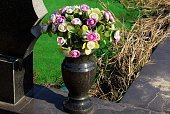 one black marble vase with a bouquet of colored artificial flowers stands on a stone slab in a cemetery
