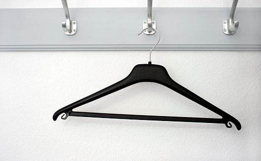 One black plastic  hanger on the wardrobe hook