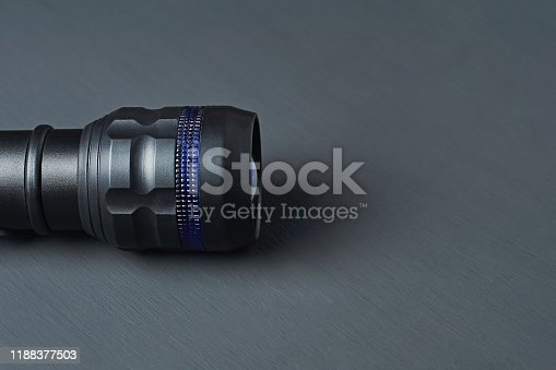 174913696 istock photo One black tactical flashlight lies on dark concrete table. Space for text 1188377503