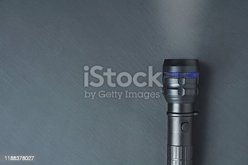174913696 istock photo One black tactical flashlight lies on dark concrete table. Space for text. Top view 1188378027