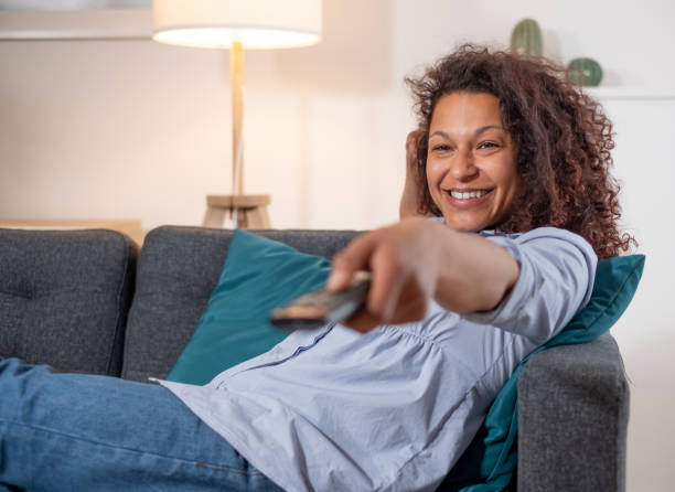 One black woman watching television on the sofa stock photo