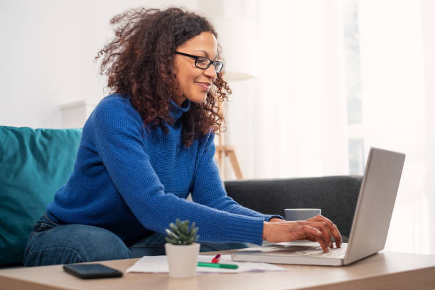 One black woman working from home using laptop stock photo