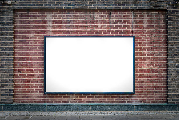 one blank board one blank billboard attached to a buildings exterior brick wall. billboard stock pictures, royalty-free photos & images