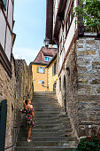 One blonde woman is climbing stairs in Creglingen town, Germany.