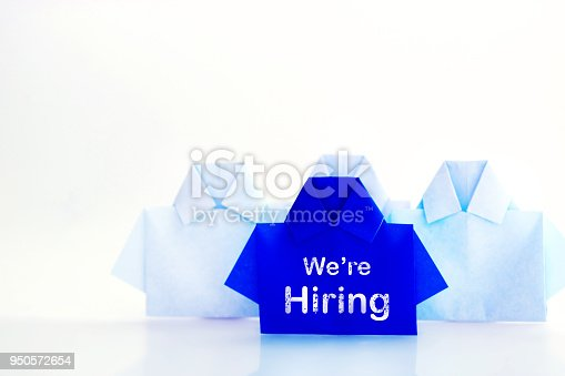 1153648747istockphoto One blue among white origami shirt paper with We're Hiring message text , the recruitment Human resource for employee unique individuality and difference or leadership concept. 950572654