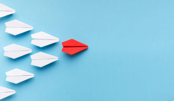 One blue paper plane leading group of white ones New trends concept. One red paper plane followed by group of white ones on blue background, copy space adulation stock pictures, royalty-free photos & images