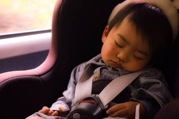 un jeune garçon endormi dans la voiture - child car sleep photos et images de collection