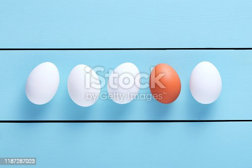 istock One brown egg lined up among white eggs 1187287023