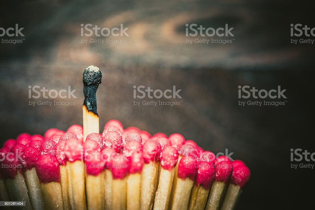 One burnes match standing out from the crowd stock photo