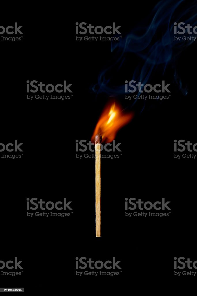 one burning match on a black background stock photo