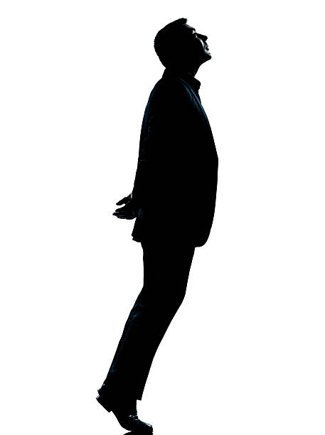 one business man silhouette tiptoe looking up stock photo