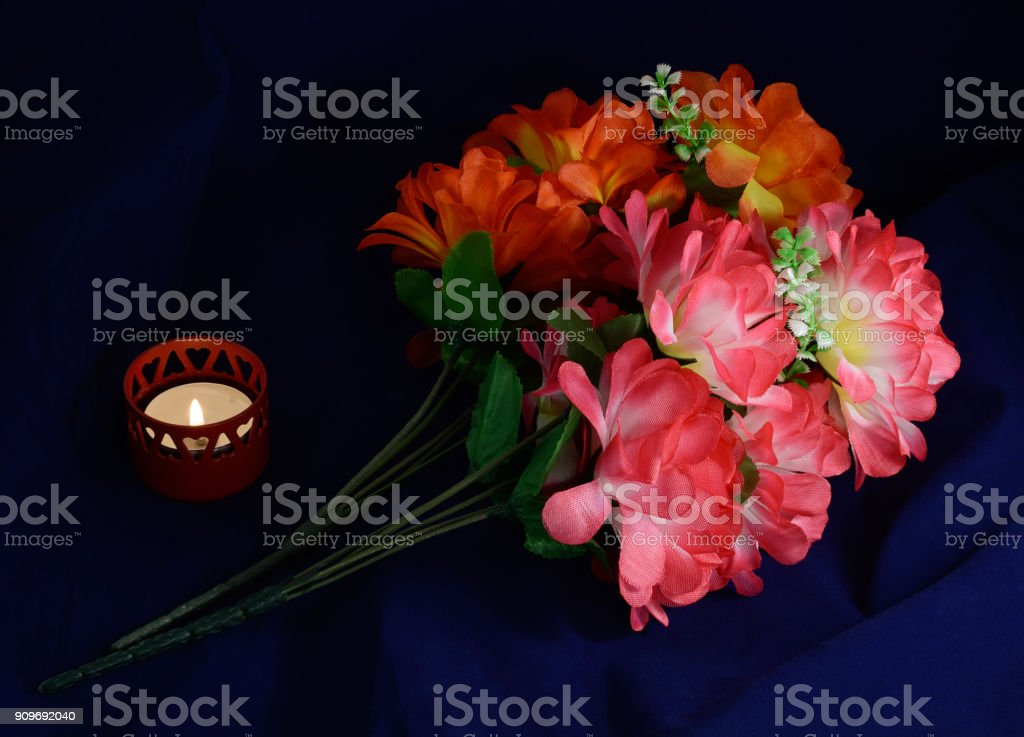 one candle artificial flowers stock photo