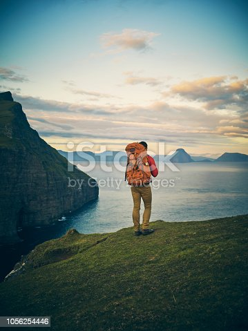 Rearview shot of a carefree unrecognizable man standing on a hill looking out to a view of a lake and mountains