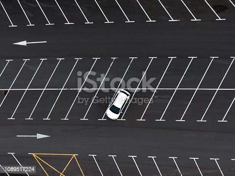 A directly above view of a lonely car in a parking lot