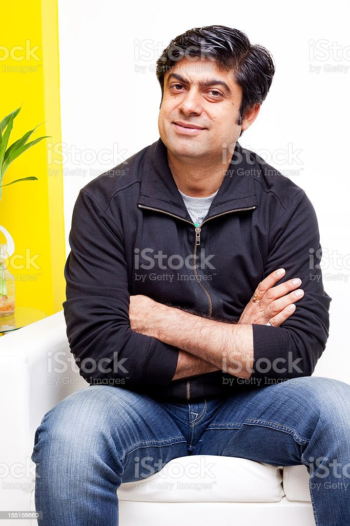 One Casual Asian Indian Man sitting on White Couch Sofa stock photo