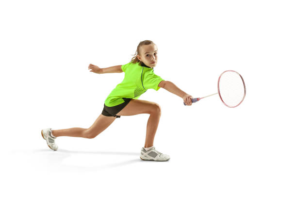 one caucasian young teenager girl woman playing Badminton player isolated on white background The one caucasian young teenager girl playing badminton at studio. The female teen player isolated on white background in motion badminton stock pictures, royalty-free photos & images